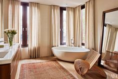 A Marc Newson–designed chair by Cappellini sits beside a Boffi tub in this Manhattan townhouse master bath.
