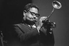 "John Birks ""Dizzy"" Gillespie (1917 – 1993)  American jazz trumpeter, bandleader, composer and occasional singer.  AllMusic's Scott Yanow wrote, ""Dizzy Gillespie's contributions to jazz were huge. One of the greatest jazz trumpeters of all time (some would say the best)' Gillespie was a trumpet virtuoso and improviser, building on style of Roy Eldridge, adding layers of harmonic complexity with beret, horn-rimmed spectacles, scat singing, bent horn, pouched cheeks and light-hearted…"