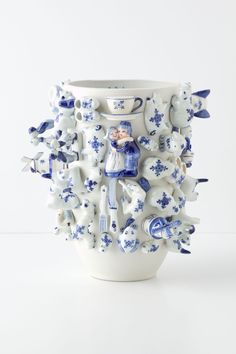 """""""Cornelis Souvenir Vase"""" is a white ceramic vase with little figures put on it to remember the specials from the country where it comes from 