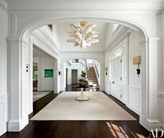 In the entrance hall, the Shelton, Mindel team offset Stern's traditional architecture with a Mauro Fabbro parchment light fixture from Casati Gallery; the mid-century ceramic-and-metal sconces are by Georges Jouve, and the wood table is a circa-1967 Carlo di Carli design for Sormani.