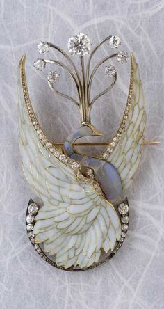 "Philippe Wolfers - A rare Art Nouveau gold, silver, plique-à-jour enamel, diamond and opal brooch, with later alterations. Designed as a swan with its wings spread, the body in opal. Probably altered in 1950 with the addition of diamonds surmounting the swan's head and the crescent moon. Signed PW on reverse and inscribed ""Ex. Unique"""