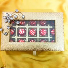 Glittery golden chocolate box with studded S-brooch. Facebook.com/1stchoicegift Homemade Chocolates, Trousseau Packing, Money Envelopes, Chocolate Box, Brooch, Fancy, Facebook, Gifts, Presents