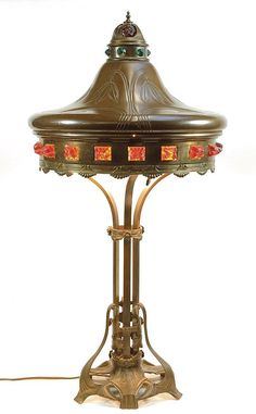 "ART NOUVEAU BRONZE TABLE LAMP having glass ""jewel"" adorned metal circular shade. Lamp has four-light feature and rests on a whiplash curve inspired base with quad foot. Height 33 inches."
