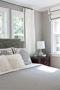 Gray bedroom features gray walls framing gray velvet headboard with silver nailhead trim accented with white and gray bedding and white and gray Greek key pillows situated in front of window dressed in white curtains with gray ribbon trim. I like the mix of curtains and shades that match. by rochelle