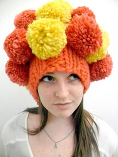 I wouldn't wear this, but bet if made in team colors, it would get worn.  No pattern for this, and it's knitted, but I would crochet a basic cap/hat, then make XXXXlg pom poms to attach on top, school/college/team colors.   [pom pom hat - Jamie McCarty]