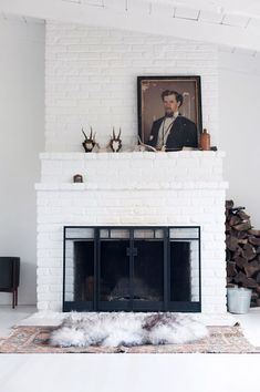 white brick fireplace with vintage portrait painting leaned on the mantle / sfgirlbybay