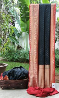 This Benares tussar is in jet black with dot-like bhuttas in gold zari all over. The contrasting pallu and border are in apple red that is intricately woven with gold zari giving it a stunning look