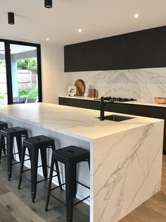 waterfall countertops, caesarstone, black cabinets, minimalist hardware on cabinets.