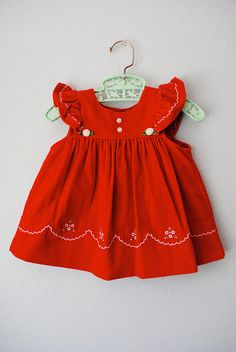 """adorable red velvet pinafore style dress with scalloped and floral embroidery. flutter ruffle sleeves at the shoulders. 4 button closure all the way down the back. would be perfect for the holiday season.  brand: no tags tag size: none ~ guesstimate 12 months measurements when flat: • shoulder to shoulder 9"""" • armpit to armpit 11 1/2"""" • length 13 1/2"""" fabric: cotton blend vintage condition: great"""