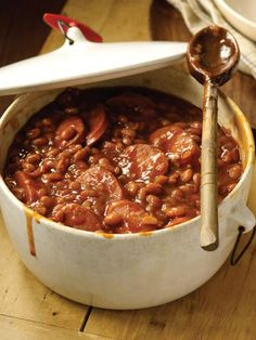 BAKED BEANS: 2 tablespoons canola oil 1 large onion, finely chopped 3 cloves garlic, finely chopped 1/2 pound smoked sausage, sliced Three 16-ounce cans pork and beans 1/2 cup ketchup 1/2 cup light molasses 1/4 cup light-brown sugar 2 tablespoons apple-cider vinegar 2 tablespoons prepared mustard Dash of hot sauce, preferably Tabasco