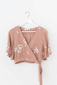 Gorgeous dusty rose woven crepe top with floral embroidered detailing and short bell sleeves. Surplice front with button snap and bow-tie closure. Cropped fit.
