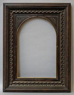 A Carved and Ebonised Italianate Style Frame, late 20th century, the arch topped spandrels with inset roundels, demi fleur sight, the hammered hollow with paterae and scrollwork in high relief, the centred cushion moulded front edge with stop fluted courses, 49.5x31.7cm (VAT charged on hammer price) - Price Estimate: £250 - £350