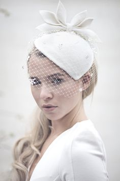 Our Siobhán hat is a an updated version of the 'Sara' design; a vintage  style wedding percher hat made in off white peachbloom felt with a small  birdcage veil. The hat is completely hand formed with the veiling being  designed to just skim the eye line.  Item details     * The hat attaches with millinery elastic and a metal comb.     * Other veiling options avaialble.     * Made to order.