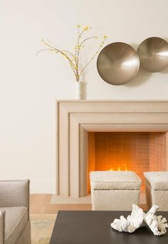Two hammered brass bowls are mounted on a wall above a cream cast limestone art deco style fireplace lined with a pair  of white cowhide storage ottomans accented with brass nailhead trim.