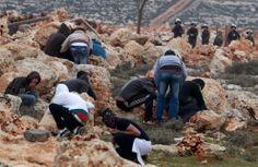06.02.2014 ZACHODNI BRZEG, Qusra, Palestyńczycy chowają się za głazami podczas starcia z żołnierzami izraelskimi. AFP PHOTO/JAAFAR ASHTIYEH