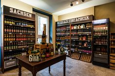 Craft Beer Store & Pub Dresden (Kunsthof). Beautifully handcraftet shelfs, dark timber, sand-colour. Photo by Thomas Schlorke