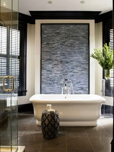 Freestanding tub with natural stone accent wall. Interior design