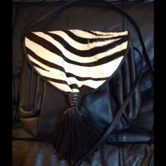 """Black Leather Zebra Print Fur Handbag This is a Susan Gail black leather handbag made in Italy. The front flap is real fur in a zebra print. There are some small places where the fur is worn as shown in pics. The leather is in pristine condition and the inside is spotless. The bag is appx. 9""""x10"""" with a 50"""" strap that can be used cross body or tied off to shorten. This bag has been cleaned and conditioned and is ready to use. Susan Gail Bags"""
