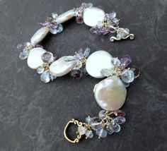 Iridescent baroque pearls and a bevy of gemstones in wonderful, watercolor shades--the Helena baroque coin pearl bracelet with aquamarine, blue topaz, and amethyst in sterling silver.  Large coin pearls (15-17mm in diameter) are hand-linked on sterling silver wire and spangled with aquamarine briolettes and rondelles, smooth pink amethyst onion briolettes and faceted squares, natural holly chalcedony rondelles, faceted moonstone rondelles, and pale blue topaz squares. This lovely bracelet…