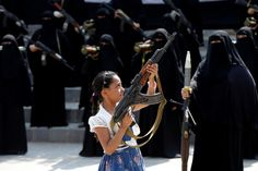 A girl holds a rifle in front of women taking part in a parade to show support for the Houthi movement in Sanaa, Yemen - by Reuters/Khaled Abdullah, Yemeni