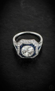 A stunning Diamond and Sapphire Engagement Ring. Set in platinum and with two halos surrounding the beautiful Old European Cut Diamond.