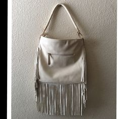 """Altar'd State Off White Fringe Hobo Purse Altar'd State Off White Fringe Hobo Purse. Great shape, never used.  NWOT!  Gold hardware. Pebbled exterior. One exterior  zippered pocket. Interior has one zippered pocket and two open pockets. Fabric lining.  Braided strap. Nice and roomy.  Strap drop 8"""". Purse Height 13"""", length 13"""", fringe length 10"""".  Great neutral!  #boho, #gypsy, #soho, #hippie, #hipster, #beige, #cream, #ivory, #nude, #western, #cowgirl, #cowboy, #altered Altar'd State Bags…"""