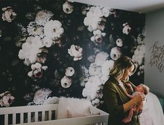 With quotes in gold modern calligraphy on the walls, blush faux fur pillows, & moody colors, this floral wallpapered nursery is truly sophisticated & beautiful!