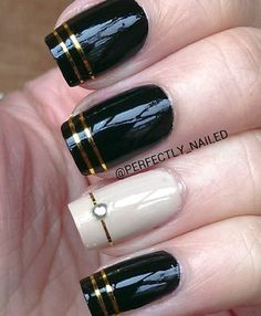 Black and white nail art design with gold stripes and embellishments.