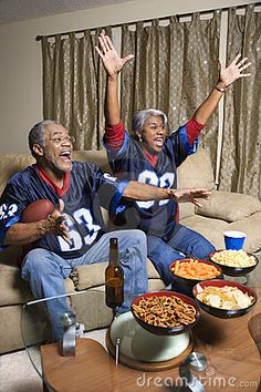 Middle-aged African-American couple watching sports on tv. by Ron Chapple, via Dreamstime