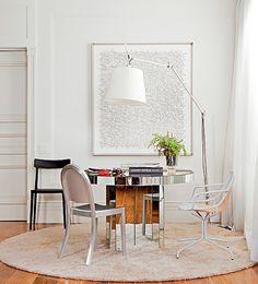 Além de paredes, cortina, quadro e luminária brancos, o ambiente de Maurício Queiroz conta com outros elementos neutros: o tapete cru, as cadeiras preta e prata e a mesa espelhada