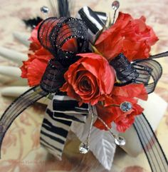 Striking black and white ribbon, with red spray roses.  Feather accents; LEDs can replace rhinestones.