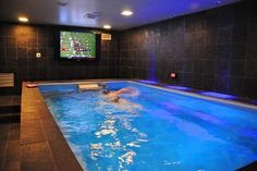 A man cave should be more than just a place to sit and watch; this one lets you stay active and still keep tabs on the big game!  The rugged textured stone on the walls, floor, and pool bring a masculine yet elegant vibe.  For more basement renovation ideas, visit http://www.endlesspools.com/tour-basement-pools.php.