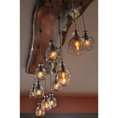 """This beautiful wood and glass custom chandelier is fashioned from a piece of real live edge Aspen that's 40"""" long. Eight blue glass globes with a pebbled texture emit a muted golden light. It's all sea foam and woodland wonder, right in your living room. Our fixtures are set for a standard 8' ceiling. They …"""