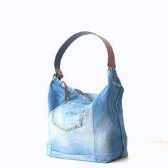 Unieke handgemaakte jeans tas van een oude spijkerbroek met leren schouderband. Voor deze schoudertas zijn de mooiste delen van een oude jeans gebruikt met nadruk op de bijzondere authentieke details.  De tas is sterk en groot genoeg voor dagelijks gebruik door de stevige jeans stof en de verstevigde bodem. De binnenzijde is gevoerd met een 100% katoenen stof en heeft een groot binnenvak met twee compartimenten voor de telefoon, sleutels en portemonnee.  Materialen: Medium jeans blauw Replay…