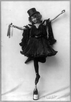 Model posed wearing black pressed pleats, top hat, and ballet shoes, standing tip-toe on champagne bottle. Photo copyrighted by Ye Rose Studio, 1904