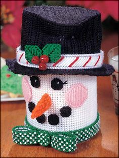 """Snowman Cookie Jar  This cheery snowman fits over a small coffee can or oatmeal can. Size: 6 3/4"""" in diameter x 8"""" tall. Stitched on 7-count plastic canvas with worsted weight yarn."""
