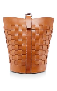 This **Trademark** bucket bag is rendered in tan calfksin with a woven design and features a snap closure with an adjustable shoulder strap.