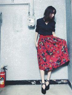 赤のスカートと黒のブラウスの相性は抜群。 女性らしい花柄のデ...|MERY [メリー]
