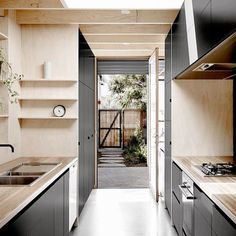 contrasting black cabinetry and plywood kitchen by robkennonarchitects located in northcote victoria