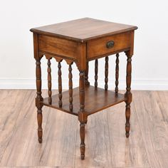 This 2 tiered end table is featured in a solid wood with a rustic dark oak finish. This side table is in great condition with intricate carved spindle details, a bottom shelf and 1 drawer. Perfect as a carved nightstand with storage for books! #traditional #tables #endtable #sandiegovintage #vintagefurniture