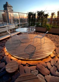 Roof terrace with modern outdoor furniture, beautiful lighting and large natural stone floor.