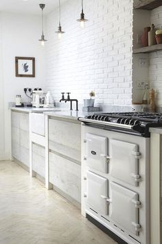 This space it's actually a studio in arestored Victorian house in SE London. No wonder! Exposed brick painted white, vintage stove, herringbone wood floors. white kitchen