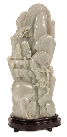 CHINESE CARVED WHITE JADE MOUNTAIN, QING DYNASTY/EARLY REPUBLIC PERIOD. 'Scholar Viewing the Waterfall in the Mountain', fully carved in the round with a bearded scholar, Wutong trees and cascading waterfall in pale green white nephrite, raised on a carved Ironwood base.