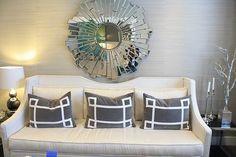 mirrored star burst mirror, greek key grey pillows, notched off-white sofa, grass cloth walls