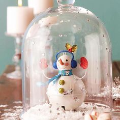 a large white bell and two small green bells, a wooden circle, wire, paper, glitter, and paint pens) and a bell-shape cloche. Set the ornament on a layer of fluffy faux snow. Embellish the cloche with rhinestone gems that look like flakes falling down the glass. Cover the scene with the cloche, and finish by scattering snowflake confetti around the arrangement.