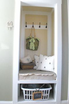 A small nook is transformed into a mudroom with storage baskets hooks.