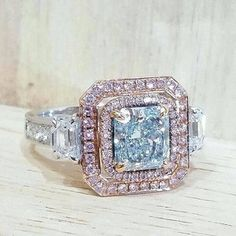 Ring in white gold with a 1.50ct rectangular modified brilliant Natural Fancy Light Greenish Blue diamond framed by pink diamonds from #PrimaGems