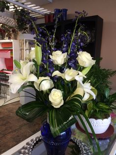 Blue delphiniums, white lilies, white roses, aspidistra leaves in case arrangement by Donna Jeffries