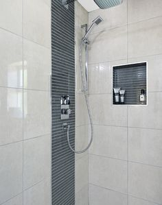 A recessed alcove in this modern shower cubicle creates the perfect space to store bathroom essentials
