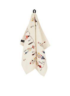Theedoek Sarjaton van iitala, door Lotta Olsson. De Zweedse illustrator staat bekend om haar unieke interpretatie van de natuur. Deze theedoek is gedecoreerd met het vapru patroon, een traditioneel bloemenpatroon met een moderne touch. Het concept en ontwerp zijn diep geworteld in folklore en ambachten.